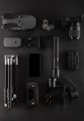 Work space videographer with laptop, digital camera, memory card, action camera, drone, remote controller, phone and camera accessory. Top view on black table background. Concept of mockup template.