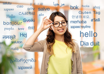 translation, education and people concept - happy asian woman or student in glasses fixed by tape over greeting words in different foreign languages