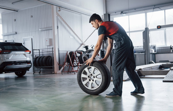 On the way to the car. Mechanic holding a tire at the repair garage. Replacement of winter and summer tires