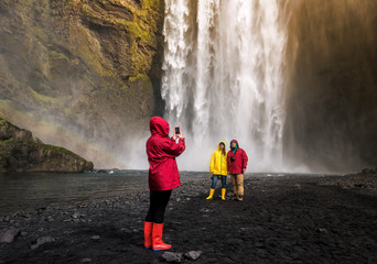 friends are photographed before a waterfall in Iceland