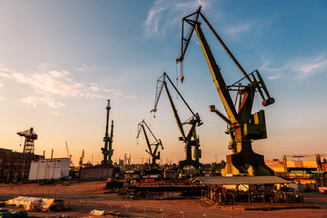 large port cranes at sunset