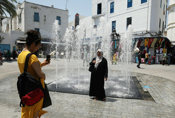 A woman poses for a picture in front of a water fountain in Tunis