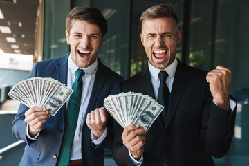Image of excited businessmen partners rejoicing and holding bunch of cash money while standing outside office center