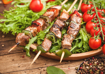 Canvas Prints Grilled pork and chicken kebab with paprika in round wooden plate of lettuce salad, on wooden background with tomatoes and spinach. Macro