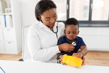 medicine, healtcare, pediatry and people concept - african american female doctor or pediatrician with stethoscope listening to baby patient on medical exam at clinic