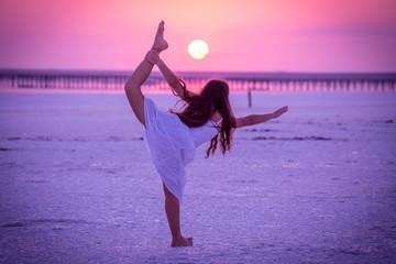Silhouette of girl doing exercises on the salt lake at sunset