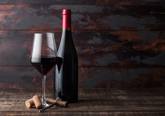 Printed kitchen splashbacks Wine Elegant glass and bottle of red wine with corks and corkscrew on dark wooden background. Natural Light