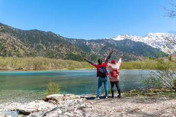 Azusa turquoise color river at Kamikochi in Northern Japan Alps with female hiker.