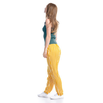 Woman in yellow pants smiling happiness standing looking on white background isolation, back view
