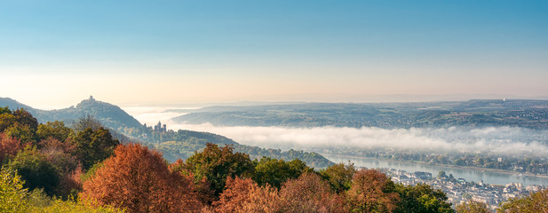 Panoramic view of the hill Drachenfels with the castle ruin, the castle Drachenburg in Siebengebirge and the town Königswinter, morning fog arose from the river Rhine valley, NRW, Germany Fototapete