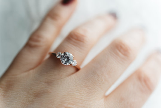 Close up of a womans hand wearing an engagement ring