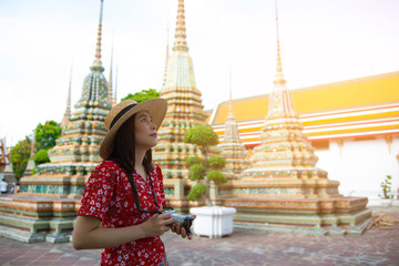 Wall Mural - Beautiful young Asian woman is taking camera and traveling into the temple in Thailand.