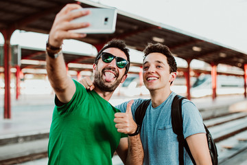 .Two brothers on the platform waiting for the train to start their summer vacation. Taking pictures together with their cellphone. Lifestyle. Travel photography