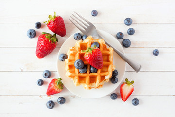 Breakfast waffles with scattered strawberries and blueberries. Top view over a white wood background.