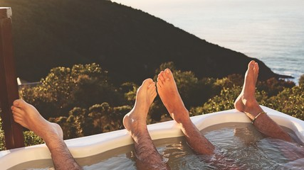 A homosexual couple enjoying a hot tub with a view.