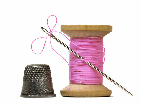 sewing threads spool with sewing needle and thimble isolated on
