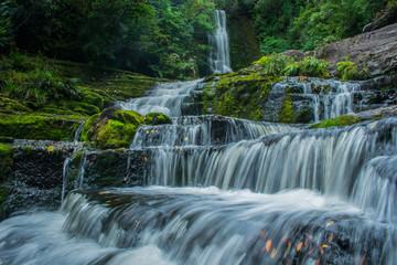 Una gran cascada al fondo y el agua corriendo en larga exposicion entre la naturaleza
