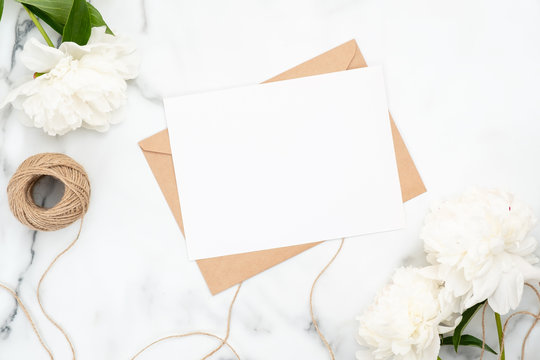 Top view blank wedding invitation card on marble background with white peony flowers and twine. Minimal flatlay style composition, concept of wedding and marriage. Beauty or fashion blog banner mockup