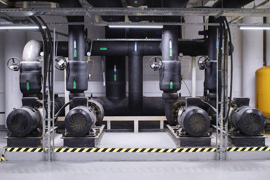 Large industrial water treatment and boiler room. Black pipes, pumps and valves. Space heating