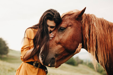 Portrait of a amazing woman with dark long hair embracing her best friend , a brown horse .
