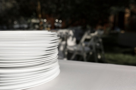 A stack of clean white plates stands on a table with a white tablecloth in the open air. Buffet at the party