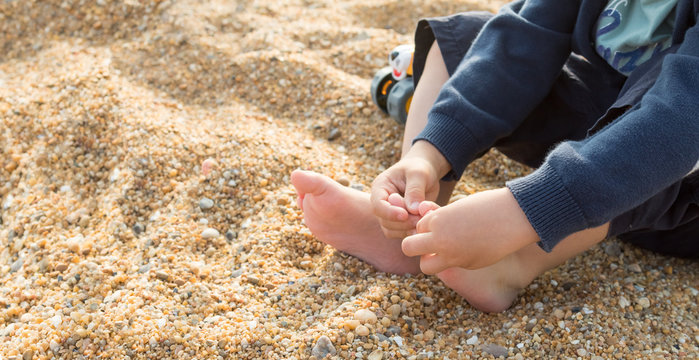 Child playing with the toes and feeling the texture of the beach sand, sensory experience