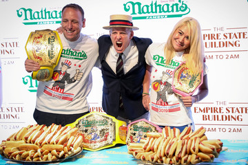 Announcer George Shea poses with current world record holders, men's champion Joey Chestnut and women's champion Miki Sudo, during the official weigh-in ceremony for the Nathan's Famous Fourth of July International Hot Dog Eating Contest at the Empire S