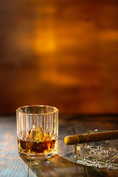 Whisky with ice and cigar on wooden background