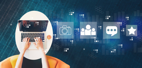 Wall Mural - Social media with person using a laptop on a white table