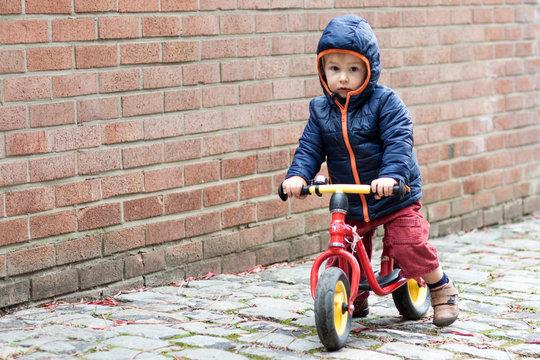 Enfant roulant en draisienne de face