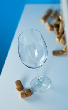 An empty wine glass on a blue background stands on a white table. Corks from wine bottles. Tasting expensive wine.