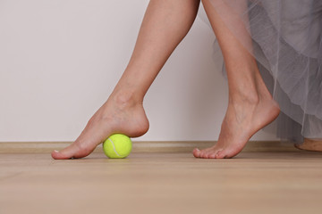 Flat Feet Correction exercises with a ball . Woman massaging her feet. Posture correction, Physical therapy.