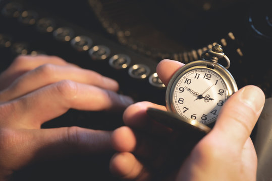 A writer is typing a book and looking on a pocket watch is his hand and is sitting by his table.