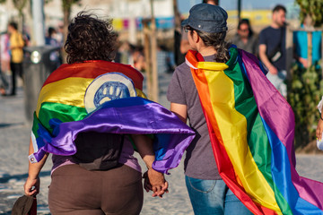 Couple of women holding hands with LGBT rainbow flags