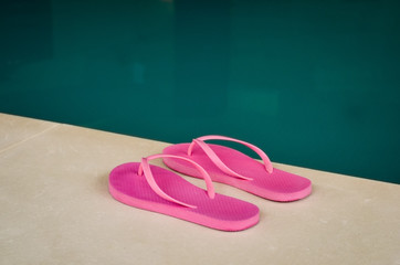 Close-up of pink flip flops at the edge of an indoor pool .