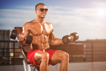 Outdoor Fitness. Muscular Men Lifting Weights at the Outdoor Gym