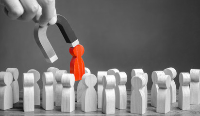 businessman pulls a red figure out from the gray crowd with a magnet. Increase team efficiency, productivity. leader manages the business and forms a team. toxic, incompetent worker. specialist