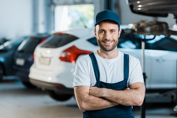 happy car mechanic standing with crossed arms in car service