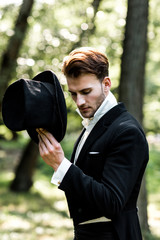 handsome aristocratic man holding hat while standing in suit