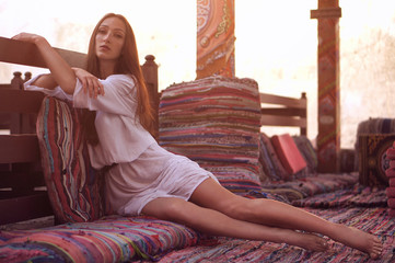 Young fashion eastern woman in white dress relaxing in traditional oriental interior in arabic town.