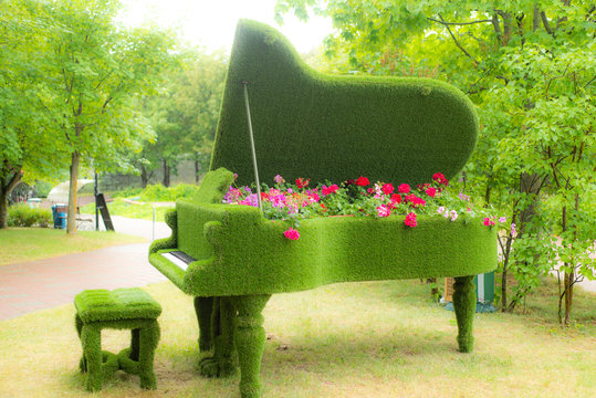 green floral piano with a variety of flowers inside, in the spring garden, blur