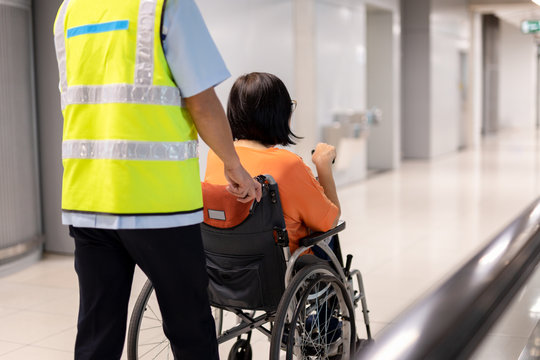 Caretaker push elderly woman on wheelchair in airport terminal.