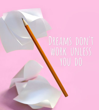 Dreams don't work unless you do - motivation work quote. pencil and paper notes. creative composition with stationery. creative concept for office supplies. work start motivation concept. soft focus