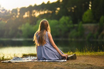 Girl blonde in a light dress sitting on a blanket and looking into the distance at sunset. Girl at sunset. Horizontal photography