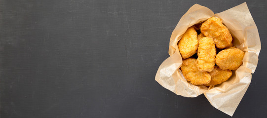 Chicken nuggets in a paper box over black background. Overhead, from above, flat lay. Copy space.