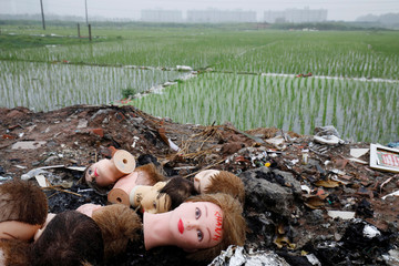 Heads of mannequins are seen by the roadside near an apartment and office project in Hanoi