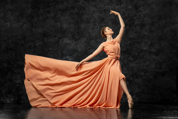Ballerina. A young dancer dressed in a long peach dress, pointe shoes with ribbons. Performs a graceful, graceful dance movement. Beautiful classic ballet. Advertising ballet studio. Volumetric photos