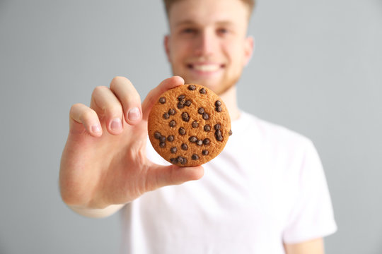 Handsome young man with tasty cookie on color background, closeup
