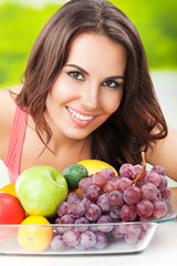 Attractive woman with plate of fruits, outdoors
