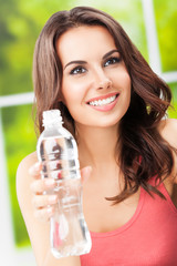 attractive young happy smiling woman with bottle of water